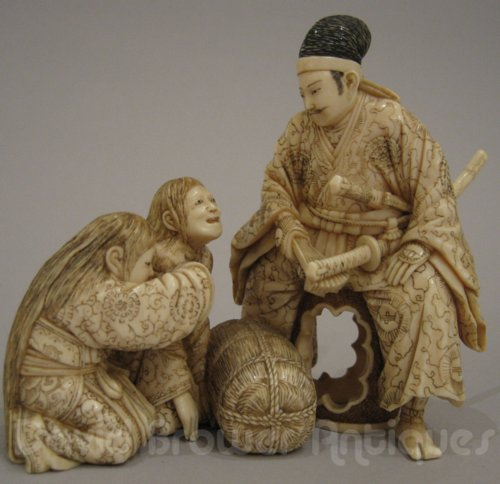 A fine Japanese ivory group of seated Samurai with 2 women