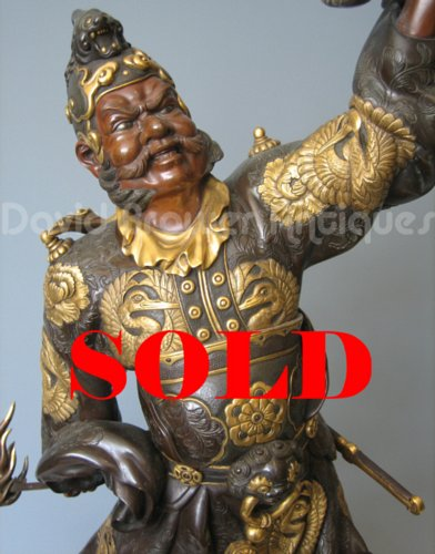 A large Japanese bronze figure of a warrior holding a Koro aloft, signed Miyao